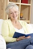 äldre kvinna läser bok hemma — 图库照片