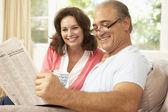 Casal sênior, lendo o jornal em casa — Foto Stock