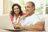 高级夫妇在家中使用的笔记本电脑 — 图库照片