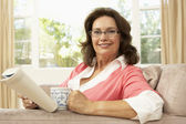 Senior Woman Reading Book With Drink At Home — Stock Photo
