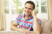 Man Relaxing On Sofa At Home — Stockfoto