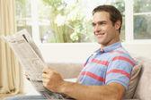 Man Reading Newspaper At Home — Stockfoto