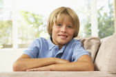 Young Boy Relaxing On Sofa At Home — Stock fotografie