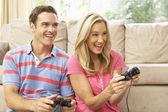 Jeune couple jouant le jeu d'ordinateur sur canapé à la maison — Photo