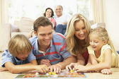 Family Playing Board Game At Home With Grandparents Watching — Stock Photo