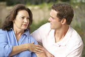 Senior Woman Being Comforted By Adult Son — Stock Photo