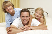 Father And Children Relaxing On Bed At Home — Stock Photo