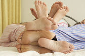 Close Up Of Family's Feet Relaxing On Bed At Home — Stock Photo