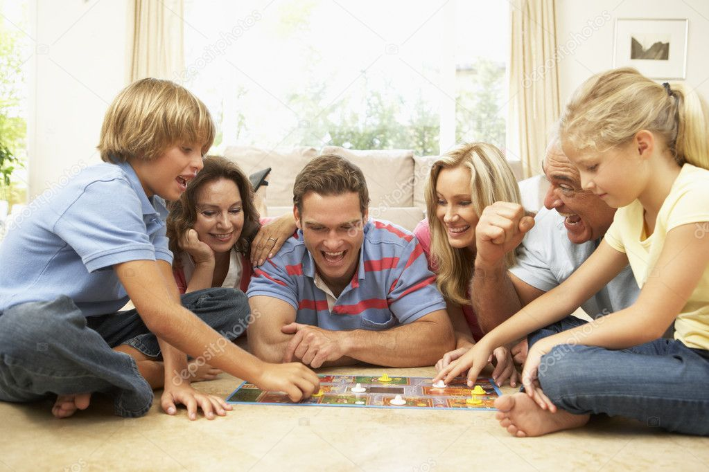 Family Playing Board Game At Home With Grandparents Watching  Stock Photo #4823872