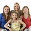 Stock Photo: Studio Portrait Of Mother Hugging Daughters