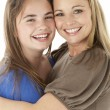 Stock Photo: Studio Portrait Of Mother Hugging Daughter