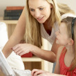 Stock Photo: Mother And Daughter At Home Using Computer