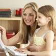Foto de Stock  : Mother And Daughter At Home Using Computer