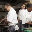 Stock Photo: Team Of Chefs Preparing Food In Restaurant Kitchen