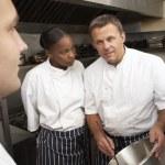 Chef Instructing Trainees In Restaurant Kitchen — Stock Photo #4835957