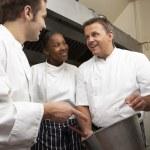Chef Instructing Trainees In Restaurant Kitchen — Stock Photo #4835960