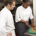 Chef Instructing Trainee In Restaurant Kitchen — Stock Photo #4835963