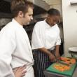 Chef Instructing Trainee In Restaurant Kitchen — Stock Photo #4835966