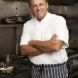 Male Chef Standing Next To Cooker In Restaurant Kitchen — Stock Photo