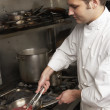 Male Chef Preparing Meal On Cooker In Restaurant Kitchen - Foto Stock