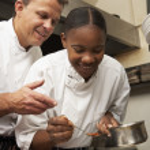 Chef Instructing Trainee In Restaurant Kitchen — Stock Photo #4835994