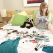 Stock Photo: Teenage Girl In Untidy Bedroom Waxing Legs
