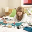 Stock Photo: Teenage Girl In Untidy Bedroom Painting Nails