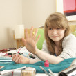 Teenage Girl In Untidy Bedroom Painting Nails - Foto Stock