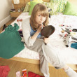 Teenage Girl Putting On Make Up In Untidy Bedroom — Stock Photo #4836029