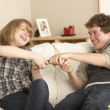 Teenage Couple Arguing Over TV Remote - Stok fotoraf