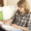Teenage Girl Studying At Home Sitting On Sofa — Stockfoto