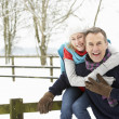Senior Couple Standing Outside In Snowy Landscape - Foto Stock