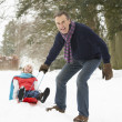Senior Couple Sledging Through Snowy Woodland - Stockfoto