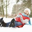 Senior WomSledging Through Snowy Woodland — Stockfoto #4836120