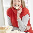 Stock Photo: Senior Woman Making Sandwich In Kitchen
