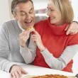 Senior Couple Sharing Takeaway Pizza In Kitchen — Stock Photo