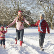 Mother Walking With Children Through Snowy Landscape - Stock Photo