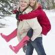 Man Giving Woman Piggyback In Snowy Woodland - Stock Photo
