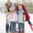 Family Pulling Sledge Through Snowy Landscape — Stockfoto