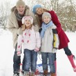 Stock Photo: Family Pulling Sledge Through Snowy Landscape