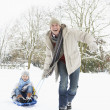 Father Pulling Son On Sledge Through Snowy Landscape — Stock Photo #4836172
