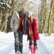 Couple Walking Through Snowy Woodland - Stock Photo
