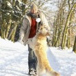 Man Walking Dog Through Snowy Woodland — Foto Stock