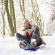 Man Sledging Through Snowy Woodland - 图库照片