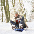Man Sledging Through Snowy Woodland - Foto Stock