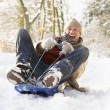 Man Sledging Through Snowy Woodland - Foto de Stock