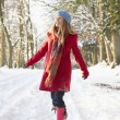 Woman Walking Through Snowy Woodland - Stock Photo