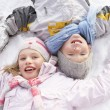 Children Laying On Ground Making Snow Angel - Stock Photo
