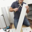Man Assembling Flat Pack Furniture - Stock Photo