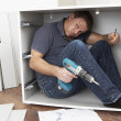 Man Trapped Whilst Assembling Flat Pack Furniture - Stock Photo